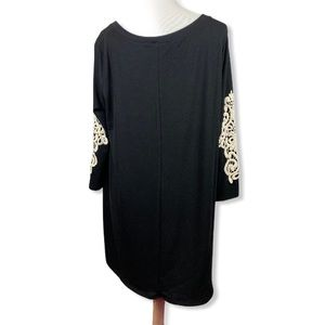 Black tunic with ornate ivory sleeve appliqué